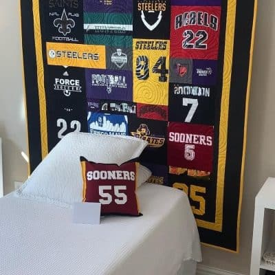 SewISaid-Custom-Memory-TeeShirt-Quilt-Collage-Pattern-with-Double-Border-Displayed-Hung-On-A-Wall-In-A-Bedroom